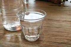 杯在桌上的纯净的被净化的矿物饮用水 库存图片