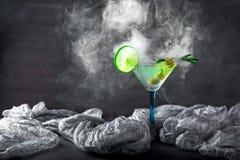 杯在桌上的鸡尾酒 橄榄、迷迭香和石灰在g 库存照片