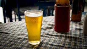 杯在桌生气勃勃和刷新的饮料的冷光啤酒 免版税图库摄影