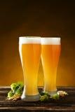 杯在棕色木背景的啤酒 免版税库存照片