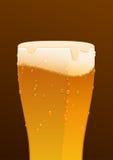 杯在棕色背景的可口新鲜的冰镇啤酒 库存照片