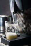 杯在榨汁器剥削者的新鲜的汁液 免版税图库摄影