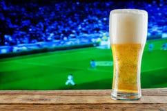 杯在橄榄球赛电视背景的啤酒 免版税库存照片