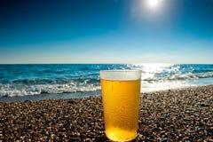 杯在海的背景的冰镇啤酒 库存图片