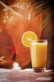 杯在海滩桌上的橙汁 库存照片