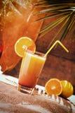 杯在海滩桌上的橙汁 免版税图库摄影