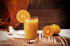 杯在海滩桌上的橙汁 免版税库存照片