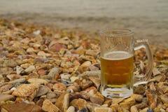 杯在海滩的啤酒 库存图片