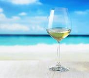 杯在海滩背景的酒 免版税库存图片
