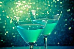 杯在深绿色彩的蓝色鸡尾酒点燃bokeh 免版税库存图片