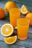 杯在灰色木背景的新鲜的橙汁 图库摄影