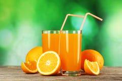 杯在灰色木背景的新鲜的橙汁 免版税库存图片