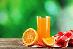 杯在灰色木背景的新鲜的橙汁 免版税图库摄影