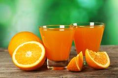 杯在灰色木背景的新鲜的橙汁 免版税库存照片