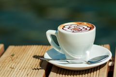 杯在热奶咖啡咖啡的艺术拿铁在海滩隔绝了外面, 穿戴女孩褂子早晨白色的咖啡杯 白色杯子拿铁热的咖啡 免版税库存照片