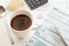杯在白色桌上的浓咖啡与收入税单形式、笔和计算器 免版税库存照片