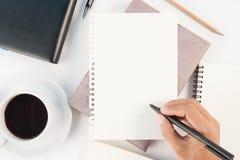 杯在白色背景的热的咖啡和人手文字笔记本 免版税图库摄影