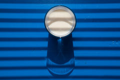杯在百叶窗前面的牛奶 免版税库存照片