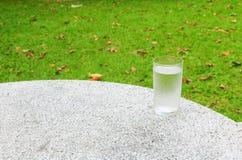 杯在磨石子地地板桌上的水冻冰块与自然backgroun 库存照片
