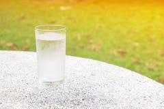 杯在磨石子地地板桌上的水冻冰块有自然背景和拷贝空间增加文本 免版税图库摄影