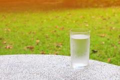 杯在磨石子地地板桌上的水冻冰块有自然背景和拷贝空间增加文本 图库摄影