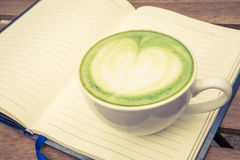 杯在笔记本的绿茶 免版税库存照片