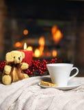 杯在红色圣诞装饰的热的饮料玩具熊蜡烛在温暖的壁炉前面的舒适被编织的格子花呢披肩 假日圣诞节 免版税库存图片