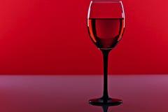 杯在红色背景的红葡萄酒 免版税库存图片