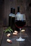 杯在老木桌上的红葡萄酒 库存图片