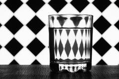 杯在背景几何形状的水 库存照片