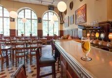 杯在著名餐馆Kvarnen的酒吧柜台的啤酒有葡萄酒家具的 免版税库存图片