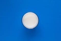 杯在蓝色木书桌上的牛奶 免版税库存图片