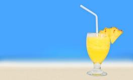 杯在表上的新鲜的菠萝汁在海滩附近 库存图片