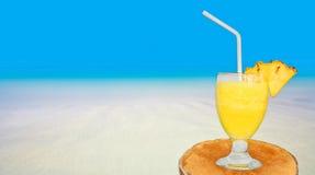 杯在表上的新鲜的菠萝汁在海滩附近 库存照片