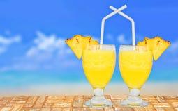 杯在表上的新鲜的菠萝汁在海滩附近 免版税库存照片