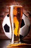 杯在表的贮藏啤酒与足球 库存图片