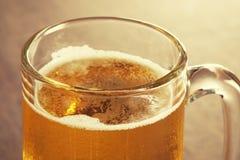 杯在被弄脏的木背景的低度黄啤酒 库存图片