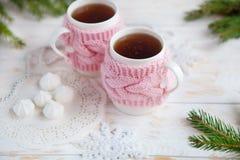 杯在被编织的杯座的热的茶与甜点和圣诞节装饰 免版税库存图片