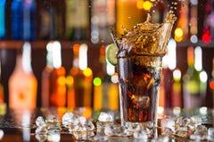 杯在酒吧书桌上的可乐有飞溅的液体 免版税库存图片