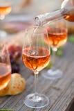 杯在野餐桌上的玫瑰酒红色 免版税库存图片
