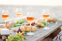 杯在野餐桌上的玫瑰酒红色 库存图片