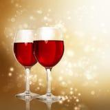 杯在闪耀的金黄背景的红葡萄酒 库存图片