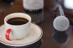 杯在音乐的热的咖啡在黑背景 免版税库存照片