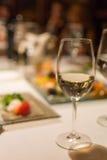 杯在餐馆桌上的白葡萄酒 库存图片