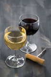 杯在黑暗的木背景的白色和红葡萄酒 免版税库存图片