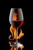 杯在黑背景的酒与火飞溅 库存图片