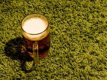 杯在绿色背景的低度黄啤酒 免版税库存照片