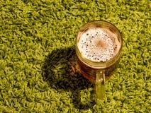 杯在绿色背景的啤酒 库存图片