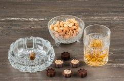 杯威士忌酒、古巴雪茄、坚果和巧克力在一张灰色木桌上 关闭上色百合软的查阅水 免版税库存照片