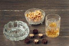杯威士忌酒、古巴雪茄、坚果和巧克力在一张灰色木桌上 关闭上色百合软的查阅水 库存图片